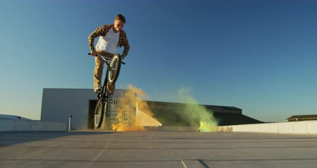 granada : Front view of a young Caucasian man riding a BMX bike and doing tricks on the rooftop of an abandoned warehouse, with yellow and orange smoke grenades in the background Vídeos