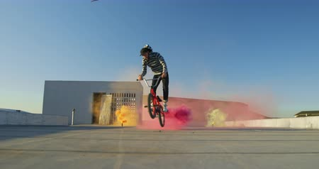 granada : Side view of a young Caucasian man riding a BMX bike and doing tricks on the rooftop of an abandoned warehouse, with a pink smoke grenade attached to the bike and colourful smoke grenades in the background Vídeos
