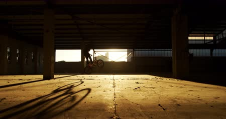 bmx : Side view of a young Caucasian man riding a BMX bike and doing tricks in an abandoned warehouse, backlit by sunlight