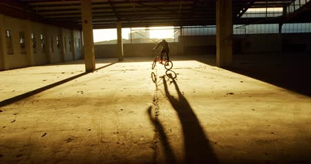 vocação : Side view of a young Caucasian man riding a BMX bike and doing tricks in an abandoned warehouse, backlit by sunlight