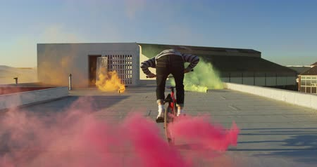 vocação : Rear view of a young Caucasian man riding a BMX bike and doing tricks on the rooftop of an abandoned warehouse, with a pink smoke grenade attached to the bike and colourful smoke grenades in the background