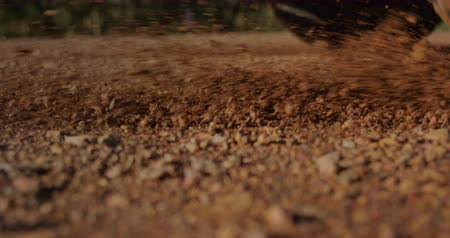 grit : Close up of back wheels of a car driving off on grit during a road trip in the sunshine, they are on a road trip Stock Footage