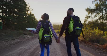 hátsó megvilágítású : Rear view of a young mixed race couple with rucksacks, talking during a trek in countryside, holding hands in the evening