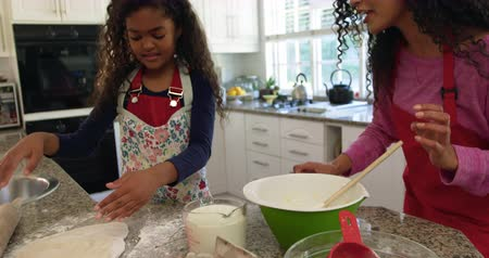 kneads : Front view of a mixed race mother in a kitchen with her young daughter at christmas making cookies, breaking an egg to add to a mixing bowl while her daughter kneads dough with her fingertips