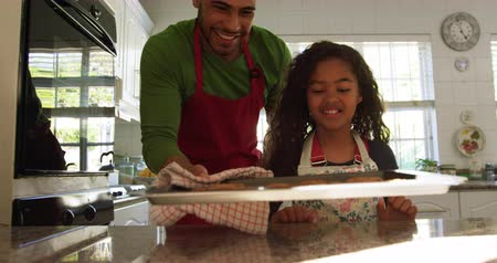 undefined : Front view of a mixed race father in a kitchen with his young daughter at christmas making cookies, taking the baking tray of cookies out of teh oven and looking at them together