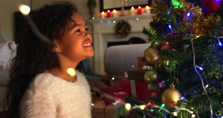мишура : Side view close up of a young mixed race girl in her sitting room at Christmas decorating the Christmas tree and smiling with joy, her father visible sitting in the background