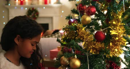 мишура : Side view close up of a young mixed race girl in her sitting room at Christmas decorating the Christmas tree and smiling with joy and excitement