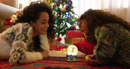 pozlátko : Side view of a mixed race mother  with her young daughter in their sitting room at christmas, lying on the floor facing each other looking at a snow globe between them and smiling to each other