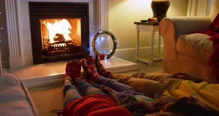 тапочка : Low section of a mixed race family and their young daughter in their sitting room at christmas, lying on the floor by the fireplace together warming their feet