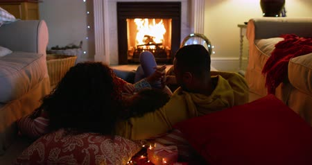terlik : Rear view of a mixed race family with their young daughter in their sitting room at christmas, lying on cushions on the floor by the fireplace warming their feet and talking
