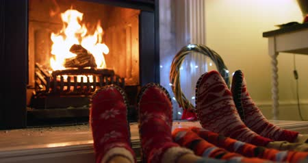 наслаждаться : Low section close up of a mixed race family in their sitting room at christmas, lying on the floor by the fireplace together warming their feet