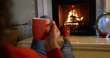 terlik : Over the shoulder view of a mixed race woman in her sitting room at Christmas, reclining in front of the fireplace, warming her feet and drinking a hot drink in a mug