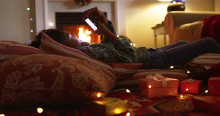 reclináveis : Side view of a young mixed race girl in her sitting room at Christmas, lying on cushions on the floor in frongt of an open fire using a smartphone