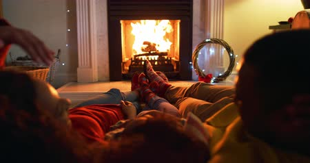 reclináveis : Rear view close up of a mixed race couple with their young daughter in their sitting room at Christmas, lying on cushions on the floor by the fireplace warming their feet and talking