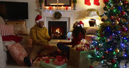 hediyeler : Side view of a mixed race couple in their sitting room at Christmas, wearing santa hats and sitting together on the floor, the man receiving a present from the woman, both laughing and then embracing