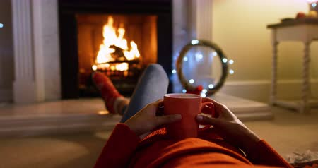 reclináveis : Low section view of a mixed race woman in her sitting room at Christmas, reclining in front of the fireplace, warming her feet and holding a hot drink in a mug
