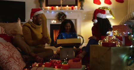 presentes : Front view close up of a mixed race family with their young daughter in their sitting room at christmas, sitting together on the floor, the couple wearing santa hats and the girl opening a present from them
