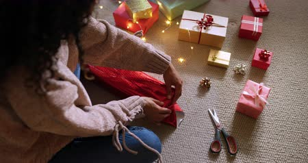 navidad regalos : High angle view of a mixed race woman in her sitting room at Christmas, sitting on a floor and wrapping presents Archivo de Video