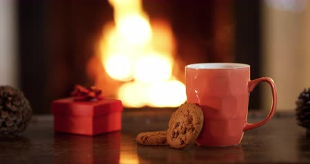 подарок : Close up of the hand of a young mixed race girl reaching and taking a cookie from the table in her sitting room at Christmas time, a mug and a small red gift box are also on the table and the flickering flames of an open fire in a fireplace are in the bac