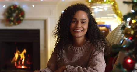 bolinhos : Portrait close up of a happy mixed race woman in her sitting room at Christmas, smiling and laughing to camera, with Christmas decorations and the flickering flames of an open fire in the fireplace in the background Stock Footage
