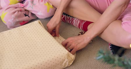 wrapping paper : Low section of a young Caucasian girl wearing a Santa hat and a pajamas wrapping presents sitting on the floor with her mother in their sitting room at Christmas time