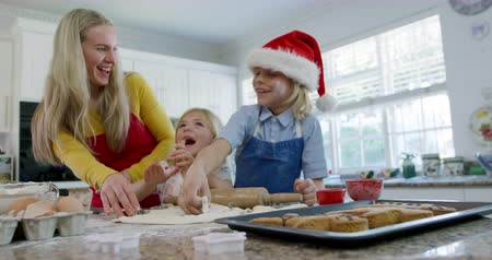draak : Front view of a happy young Caucasian mother with her young daughter and son in their kitchen at Christmas time making cookies, having fun using cookie cutters to cut shapes in rolled dough, the son is wearing a Santa hat