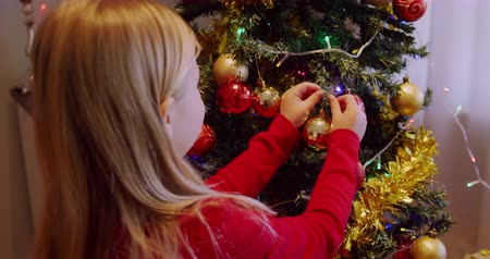 мишура : Rear view close up of a young Caucasian girl decorating the Christmas tree in her sitting room at Christmas time Стоковые видеозаписи