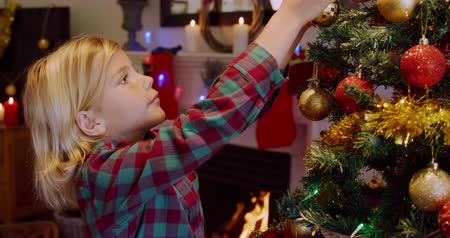meninos : Side view of a young Caucasian boy decorating the Christmas tree in his sitting room with baubles at Christmas time