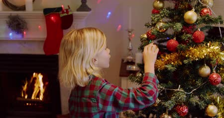 pozlátko : Side view of a young Caucasian boy decorating the Christmas tree in his sitting room with baubles at Christmas time