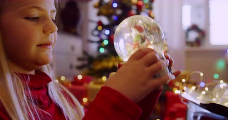 snow globe : Side view close up of a young Caucasian girl holding and shaking a snow globe in the sitting room at Christmas time and looking at it, a decorated Christmas tree in the background Stock Footage