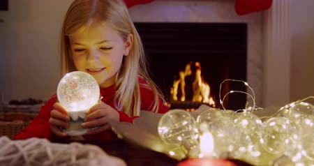 snow globe : Front view of a young Caucasian girl holding a snow globe in the sitting room at Christmas time, smiling, with an open fire burning in the fireplace behind her