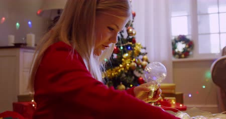 pozlátko : Side view of a smiling young Caucasian girl holding fairy lights in the sitting room at Christmas time and looking at them, a decorated Christmas tree in the background