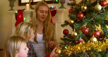 мишура : Side view of a young Caucasian woman and her young son and daughter decorating the Christmas tree together in their sitting room at Christmas time Стоковые видеозаписи