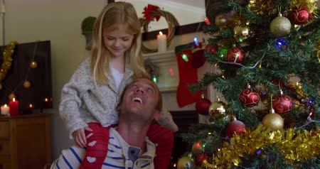önemsiz şey : Front view of a middle aged Caucasian man with his young daughter sitting on his shoulders decorating the Christmas tree in their sitting room