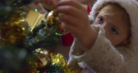 önemsiz şey : High angle view of a smiling young Caucasian girl wearing a Santa hat decorating the Christmas tree in her sitting room, reaching up to hang a bauble