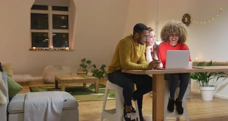 spare : Front view of a young mixed race man and woman sitting at a table with a young Caucasian woman between them, talking and looking at a laptop computer together in the sitting room of an apartment