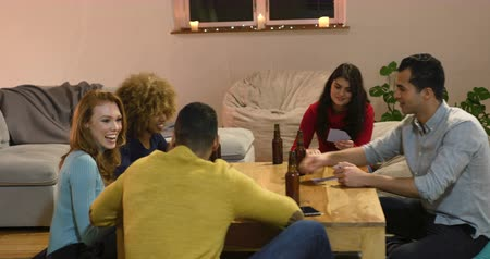 扱う : Front view of a group of five young multi-ethnic male and female friends sitting around a table playing cards and drinking bottles of beer in the sitting room of an apartment at night, one man dealing