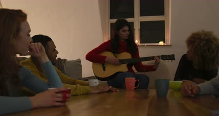 dinleme : Front view of a young Caucasian woman playing guitar with a group of four young multi-ethnic male and female friends sitting around a table listening and drinking coffee in the sitting room of an apartment at night Stok Video