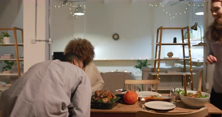 salle à manger : Front view of a group of young multi-ethnic male and female friends bringing dishes of food and sitting down at a table for a roast turkey dinner at home for Thanksgiving