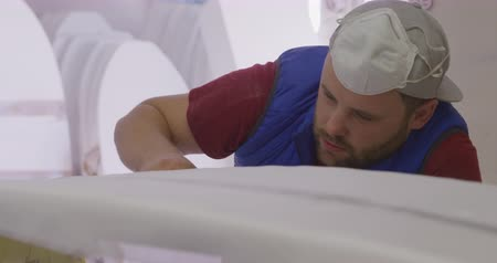 vocação : Front view close up of a millennial Caucasian male surfboard maker in his studio, inspecting a surfboard during the manufacturing process Vídeos