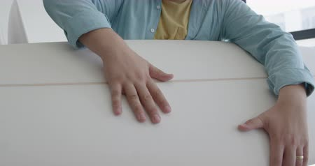 készítő : Front view close up of a millennial Caucasian male surfboard maker in his studio, holding and inspecting the surface of a new surfboard with his hands