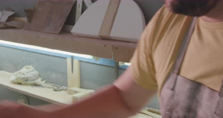 készítő : Front view close up of a millennial Caucasian male surfboard maker in his studio, sanding down a surfboard during the manufacturing process