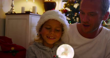 snow globe : Front view of a happy middle aged Caucasian father sitting on the floor with his young son holding a snow globe and wearing a Santa hat, in their sitting room at Christmas time Stock Footage
