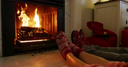 тапки : Low section of the legs of a Caucasian couple lying on the floor warming their feet together in front of an open fire in the fireplace in their sitting room at Christmas time