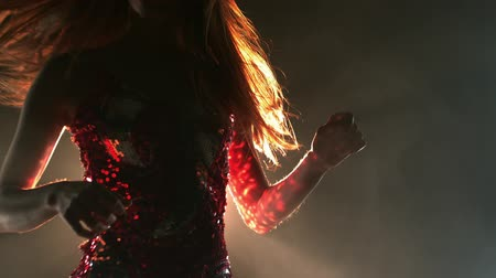 iluminado para trás : Front view close up of a young Caucasian woman dancing, wearing a sequin dress, back lit against a black background