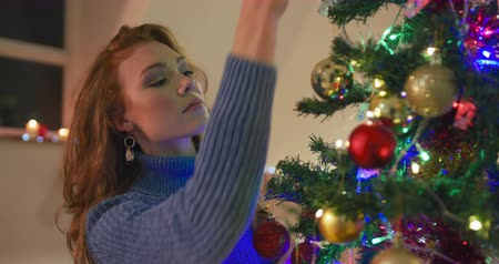 önemsiz şey : Side view close up of a smiling pretty young redhead Caucasian woman decorating a Christmas tree at home with baubles