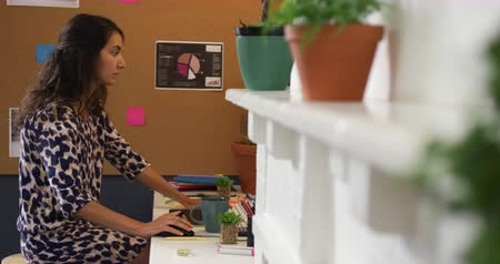 designing : Side view of a millennial Caucasian woman working in the office of a creative business, sitting at a desk using a desktop computer Stock Footage