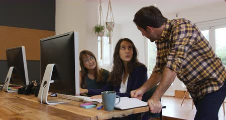 designing : Side view of a millennial Caucasian man and two women working in the office of a creative business, talking and using desktop computers
