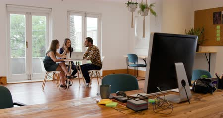 designing : Front view of a millennial Caucasian man and two women working in the office of a creative business, sitting at a table using a laptop computer and talking