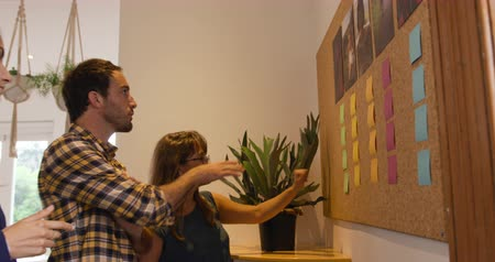 agência : Side view of a millennial Caucasian man and two women working in the office of a creative business, brainstorming at a board with sticky notes on it Vídeos